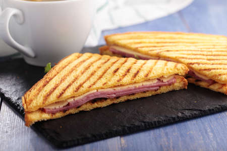 toasted sandwich: Sandwiches with ham, cheese, lettuce, grilled toasts, and a cup of coffee