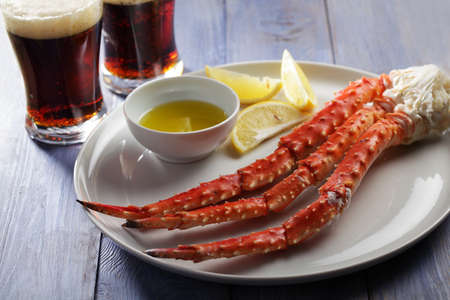 crab legs: Red king crab legs with lemon and beer on a rustic table