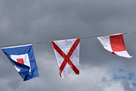 international flags: International maritime signal flags Uniform, Victor, and Whiskey against cloudy sky Stock Photo