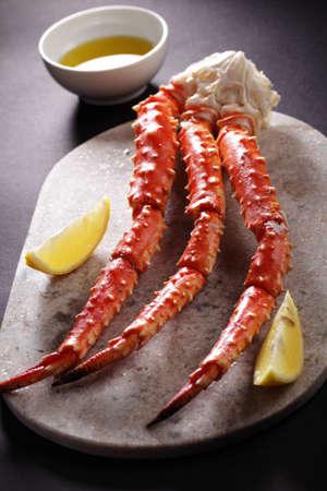 cangrejo: patas de cangrejo real rojo con el limón en una tabla de cortar mármol
