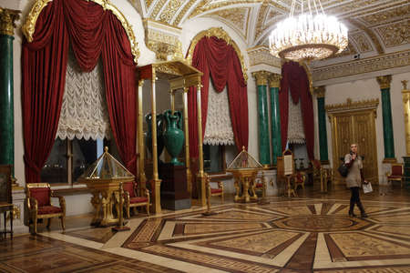 bartolomeo rastrelli: St. Petersburg, Russia - December 10, 2015: Tourist with audio-guilde in the Malachite room of Winter Palace. Built in 1762 by design of Bartolomeo Francesco Rastrelli, now the palace is main building of the State Hermitage Museum