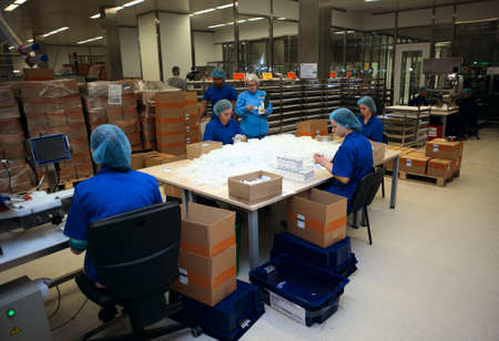 pharmaceutical plant: St. Petersburg, Russia - September 24, 2015: Workers packing the injections in the Solopharm plant. The new modern pharmaceutical plant was built in accordance with Good Manufacturing Practice standards