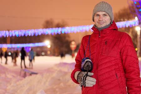 skating rink: Mature man with skates against a skating rink