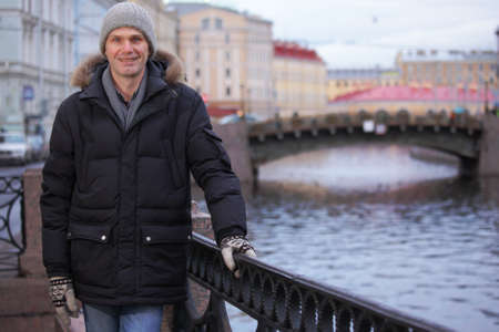 embankment: Mature man in winter clothes at the embankment of Moika river in St. Petersburg, Russia