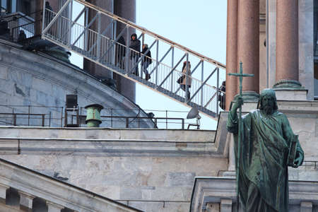 apostle: St. Petersburg, Russia - January 5, 2016: Tourists ascending to the colonnade of St. Isaacs cathedral. Sculpture of apostle Philip created by Giovanni Vitali is visible on the front
