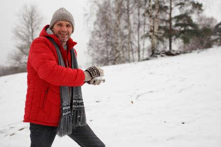 boule de neige: homme d'�ge m�r faisant boule de neige au cours de combat de boules de neige Banque d'images
