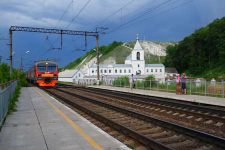 commuter train: Divnogorie, Voronezh region, Russia - June 8, 2014: Commuter train arriving to the platform against the Divnogorsky male monastery. The monastery was founded in 1650