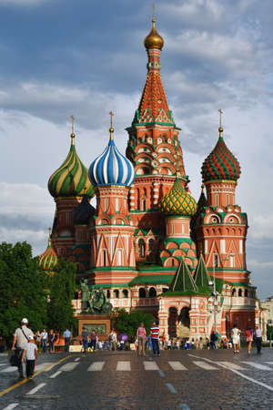 intercession: Moscow, Russia - July 2, 2014: People walking in front of St. Basils Cathedral on Red Square. The Cathedral is listed as UNESCO World Heritage site