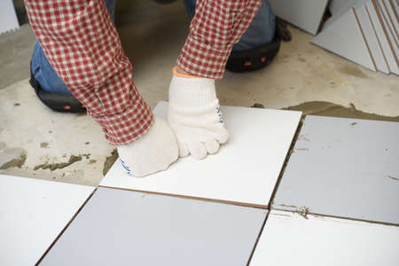 kneecap: Tiler installs ceramic tiles on a floor