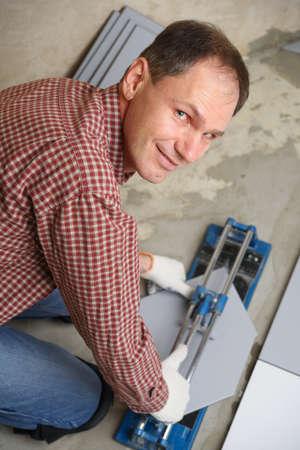 tile cutter: Tiler cutting ceramic tiles during floor installation Stock Photo