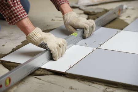 瓦職人が床にセラミック タイルをインストールします。 写真素材