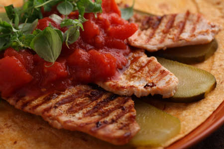 grilled food: Grilled chicken meat with pickled cucumbers, tomato, and marjoram on a flatbread