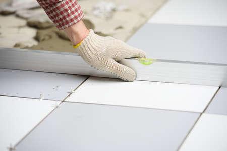 ceramic tiles: Tiler installs ceramic tiles on a floor