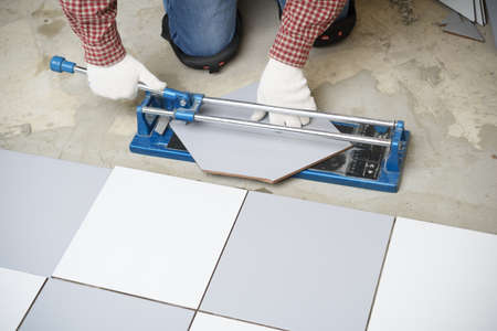 redesign: Tiler cutting ceramic tiles during floor installation Stock Photo