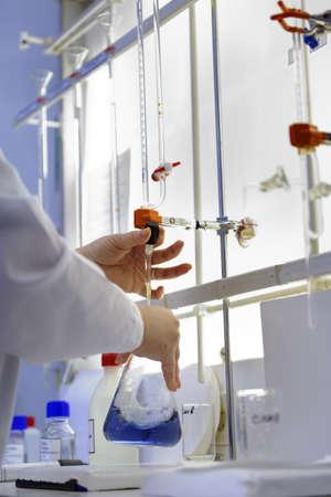 bureta: San Petersburgo, Rusia - 25 de febrero de, 2016: Svetlana Semenova participa en el concurso de habilidades profesionales entre los técnicos de análisis químicos. El concurso se lleva a cabo por la empresa de servicios públicos de agua municipal Vodokanal