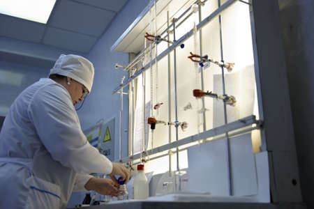 titration: St. Petersburg, Russia - February 25, 2016: Svetlana Semenova participates in the professional skills contest among chemical analysis technicians. The contest is held by the municipal  water utility company Vodokanal Editorial