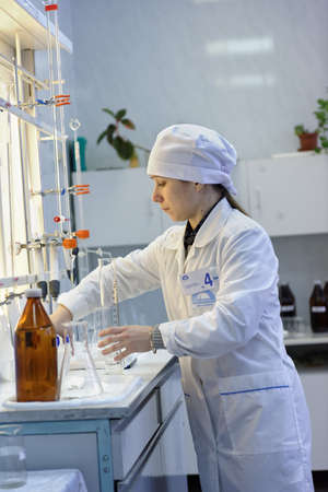 bureta: St. Petersburg, Russia - February 25, 2016: Olga Agarkova participates in the professional skills contest among chemical analysis technicians. The contest is held by the municipal  water utility company Vodokanal Editorial
