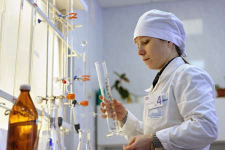 titration: St. Petersburg, Russia - February 25, 2016: Olga Agarkova participates in the professional skills contest among chemical analysis technicians. The contest is held by the municipal  water utility company Vodokanal Editorial