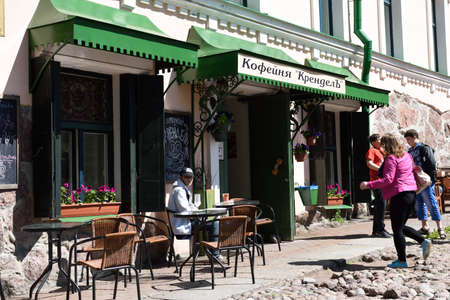 founded: Vyborg, Russia - June 6, 2015: People resting in the street cafe Krendel offering coffee and sweet pastry. The cafe was founded in 1877 Editorial