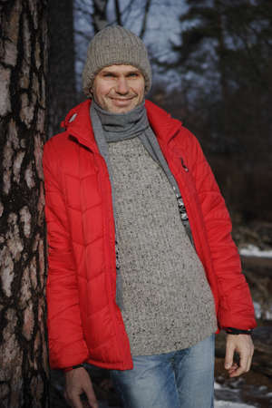 blue grey coat: Mature man in winter clothes under a pine tree Stock Photo