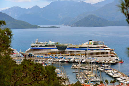 cater: Marmaris, Turkey - May 1, 2014: Cruise ship AIDAdiva in the port of Marmaris. AIDA ships cater to the German-speaking market, and has 94% average guests satisfaction rate