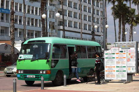 intercity: Larnaca, Cyprus - March 18, 2016: People at the intercity bus arrived to Finikoudes bus stop. Larnaca is the third largest city of Cyprus