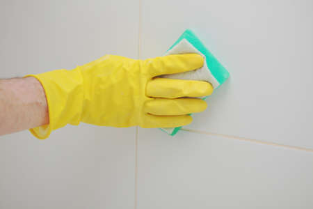 tiled wall: Cleaning tiled wall in a bathroom using cleaning sponge