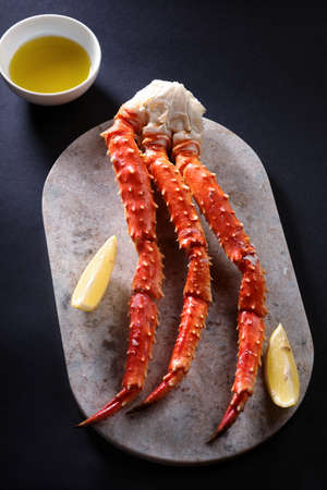 crab legs: Red king crab legs with lemon on a marble cutting board