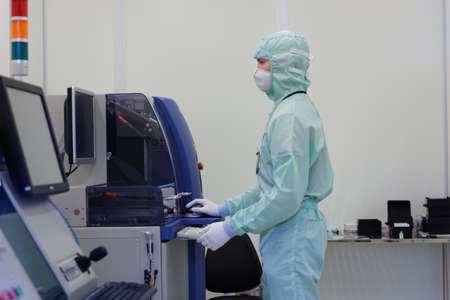 """St. Petersburg, Russia - April 18, 2016: Man in cleanroom suite working in clean room at JSC """"Avangard"""". It is Russia's leading company in radio electronics and microsystems engineering"""