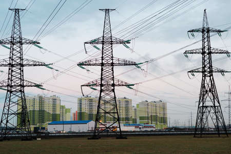 residential structures: St. Petersburg, Russia - April 22, 2016: Power line pylons against new apartment buildings in outskirts. Often new residential structures in Russia is located next to power lines