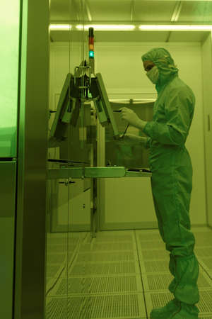 man in suite: St. Petersburg, Russia - April 18, 2016: Man in cleanroom suite working in clean room at JSC Avangard. It is Russias leading company in radio electronics and microsystems engineering