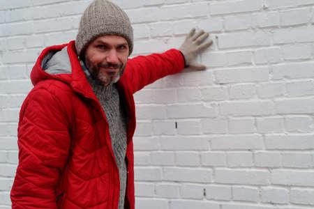 ropa de invierno: Hombre maduro en ropa de invierno contra la pared de ladrillo