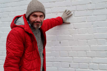 winter clothes: Mature man in winter clothes against brick wall
