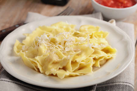 shredded cheese: Finnish ravioli with shredded Parmesan cheese and tomato sauce Stock Photo