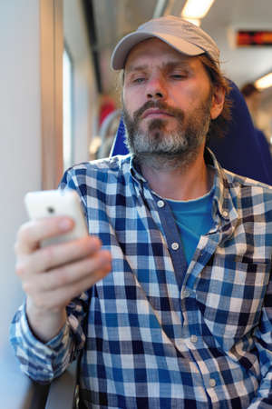 commuter train: Mature man with mobile phone in a commuter train Stock Photo