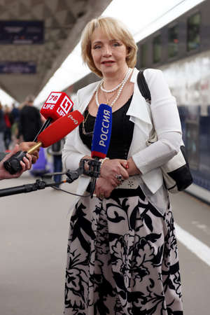 railroad station platform: St. Petersburg, Russia - May 28, 2016: President of the Mikhail Ulyanovs foundation Elena Ulyanova talks with press at the double-decker train Mikhail Ulyanov in the day of its first departure from St. Petersburg to Adler