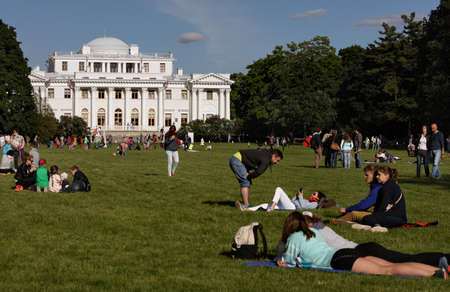 buttery: St. Petersburg, Russia - June 4, 2016: People resting on the Buttery Meadow against the Elagin Palace in the city park. The name of the meadow is derived from Russian name for Shrovetide carnival
