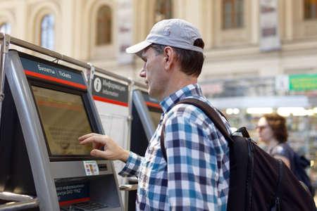 St. Petersburg, Russland - 17. Juli 2016: Mann Kauf der S-Bahn-Tickets mit Automaten in Baltiysky Bahnhof. Die Fahrkartenautomaten wurde 2009 hier installiert Editorial
