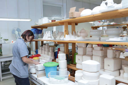 manufactory: St. Petersburg, Russia - August 9, 2016: Worker of Imperial porcelain manufactory at workplace. Founded in 1744 by order of Empress Elisabeth, now the factory produces about 4000 items