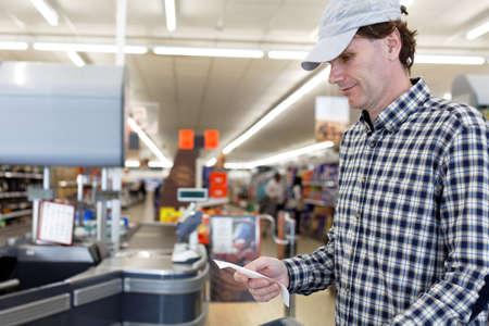 cash receipt: Buyer looks at the cash receipt in a supermarket