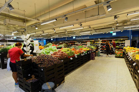 owned: Helsinki, Finland - August 21, 2016: People in the K-Supermarket in Kamppi center. Owned by Kesko company, the K-food store chains include  K-market, K-supermarket, K-citymarket and K-extra