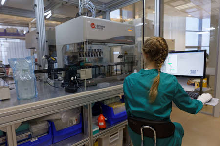 throughput: St. Petersburg, Russia - November 16, 2016: Researcher at work with automated station of selection of cultivation condition in the High-Throughput Biotechnology Laboratory of BIOCAD. It is one of the world`s few full-cycle drug development and manufacturi Editorial