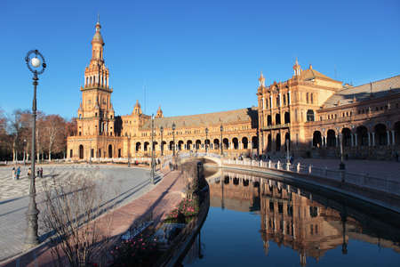 spanish architecture: Seville, Spain - January 3, 2012: People walking and making photos on Plaza de Espana. Built in 1928, Plaza de Espana is a landmark example of the Renaissance Revival style in Spanish architecture