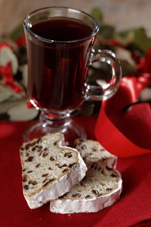 Slices of Christmas stollen and a glass of mulled wine on a rustic table Stock Photo