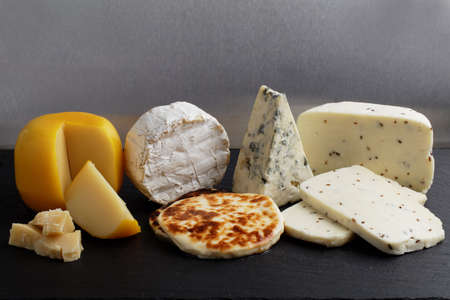 Collection of cheeses on a slate cutting board against gray background Stock Photo