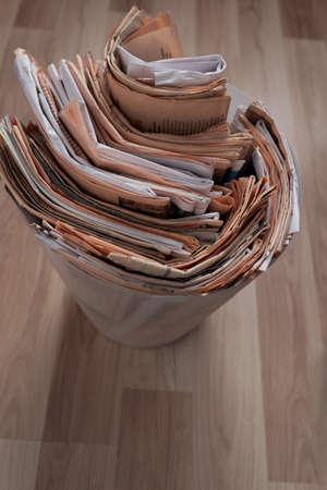 papelera de reciclaje: periódicos viejos en la papelera de reciclaje sobrecargada Foto de archivo