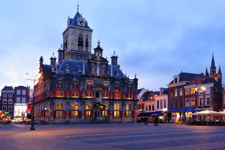 Delft, Netherlands - January 3, 2017: People on the Markt square in front of the City Hall. Originally built in 1620, it was heavily changed over the centuries and was restored in the 20th century to its Renaissance appearance