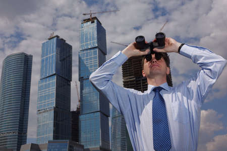 Businessman looking forward through binoculars against skyscrapers under construction