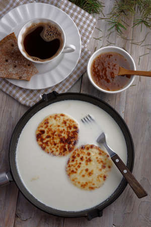 chicouté: Swedish breakfast with mini farmer cheeses in an iron cooking pan, cloudberry jam, and a cup of coffee