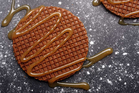 Stroopwafels with caramel sauce on a slate surface Stock Photo